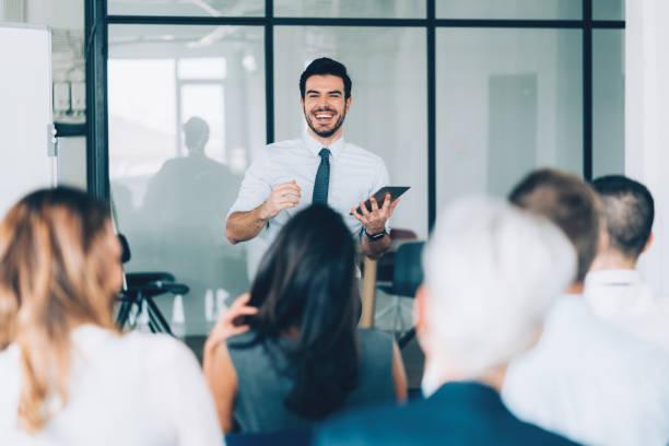 Homme d'affaire face à plusieurs employés dans une salle de réunion