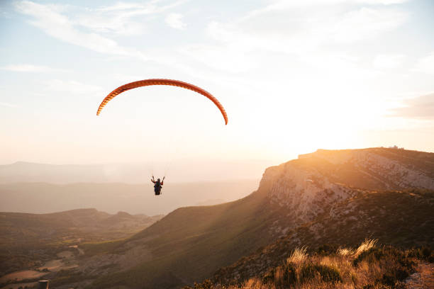Parapente dans les montagnes au coucher de soleil