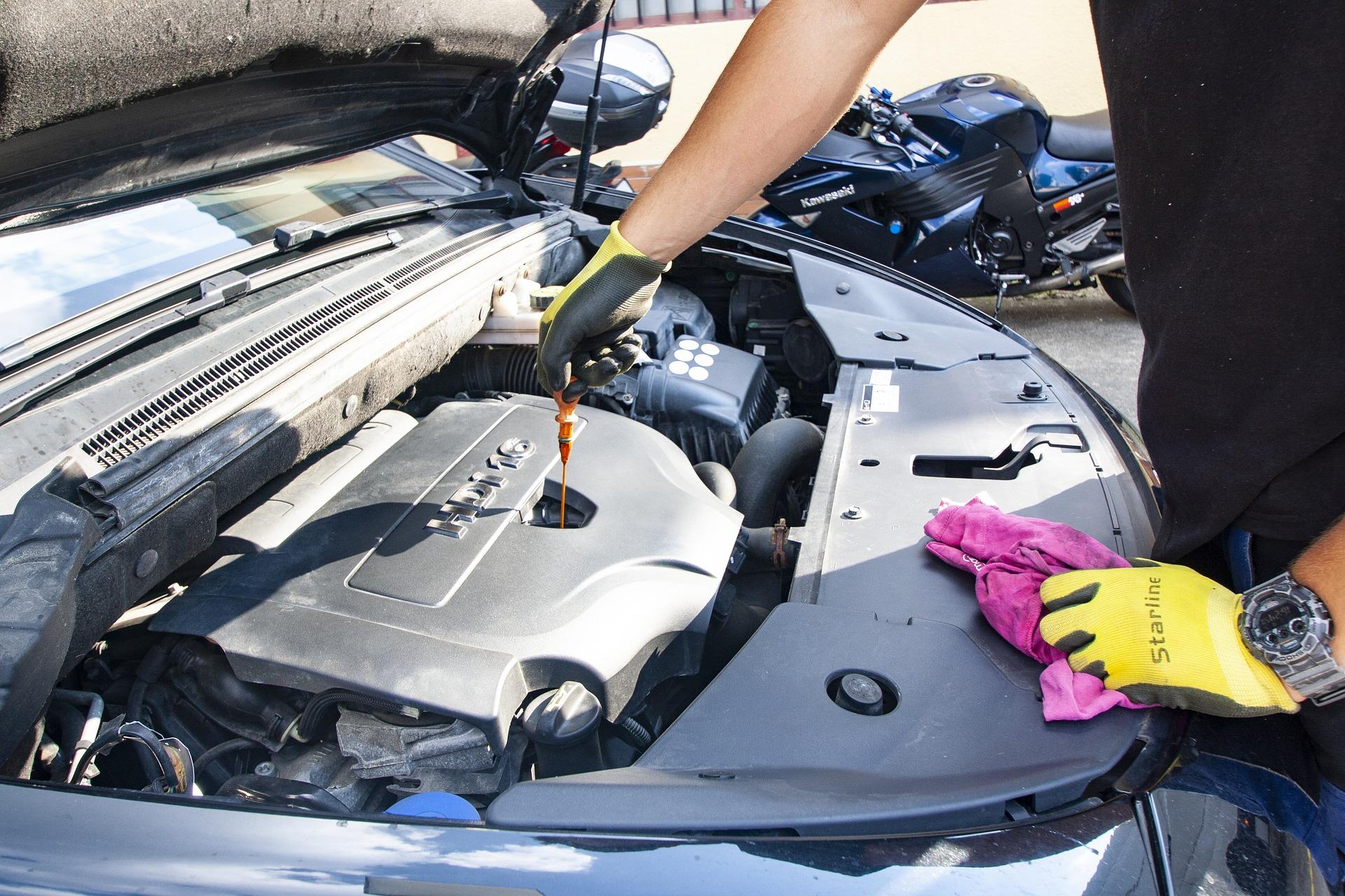 Personne qui vérifie le niveau d'huile d'une voiture