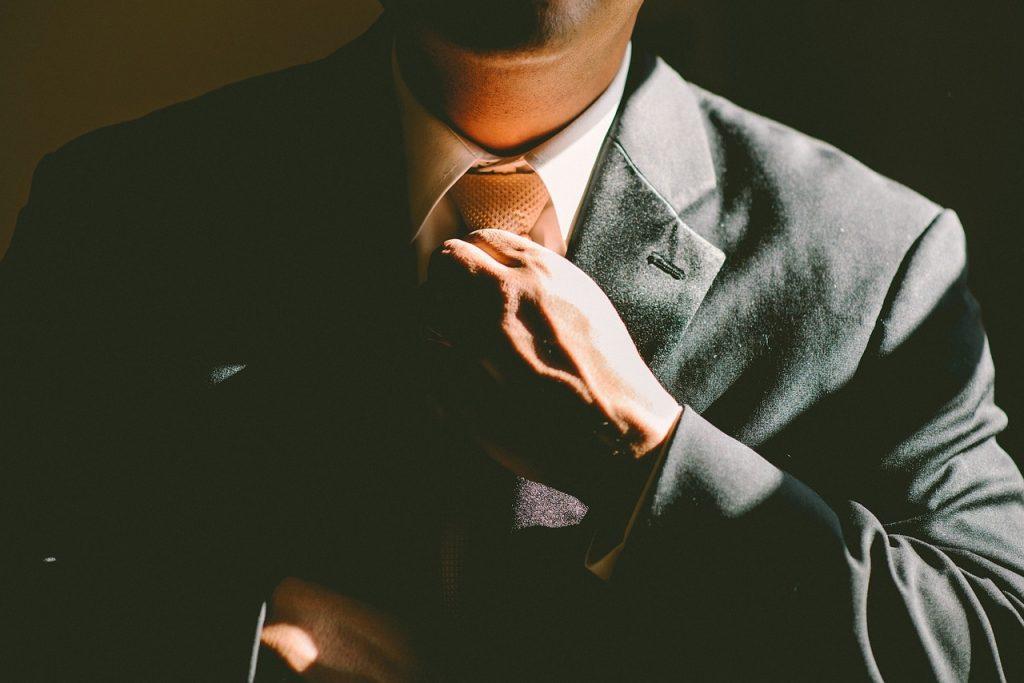 homme portant un costume foncé et une chemise blanche ajustant sa cravate