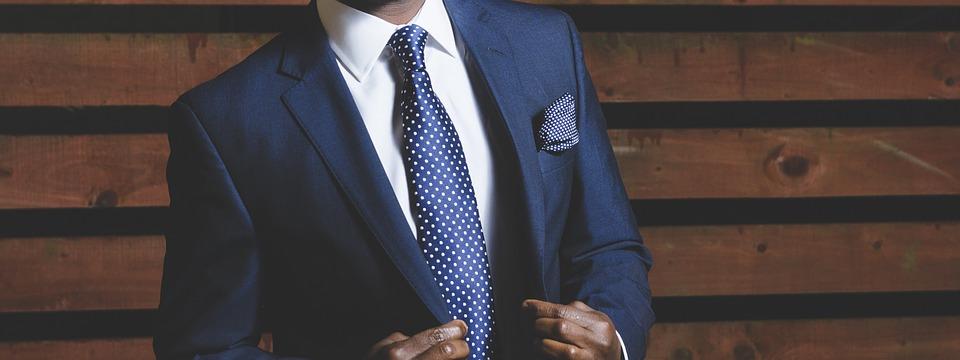 homme portant un costume bleu marine avec une cravate bleu marine et une chemise blanche