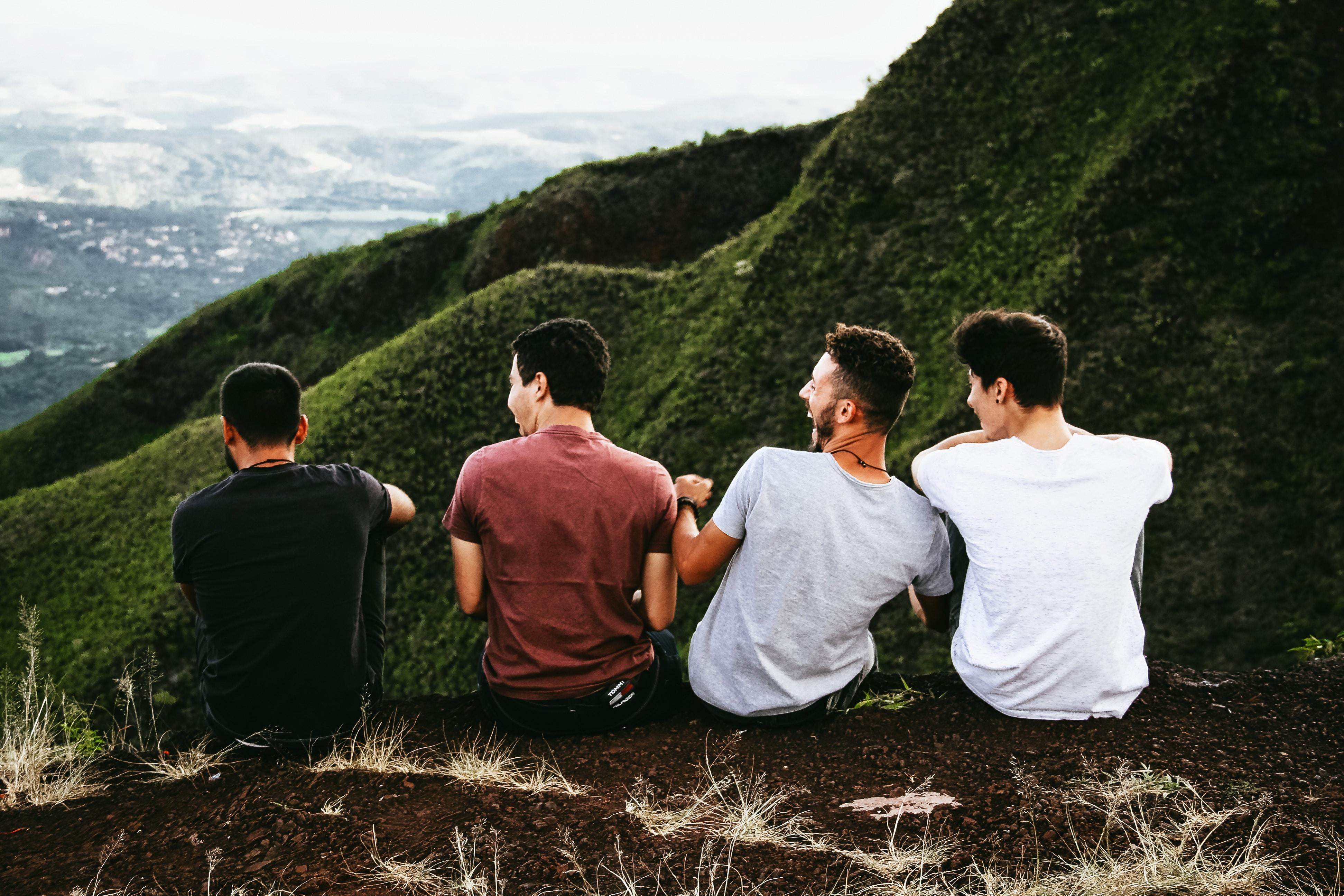 4 jeunes hommes riant ensemble assis sur le haut d'une montagne