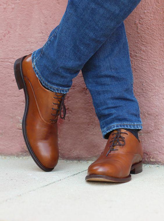 vue sur les pieds d'une homme portant un jean bleu et des richelieu marron
