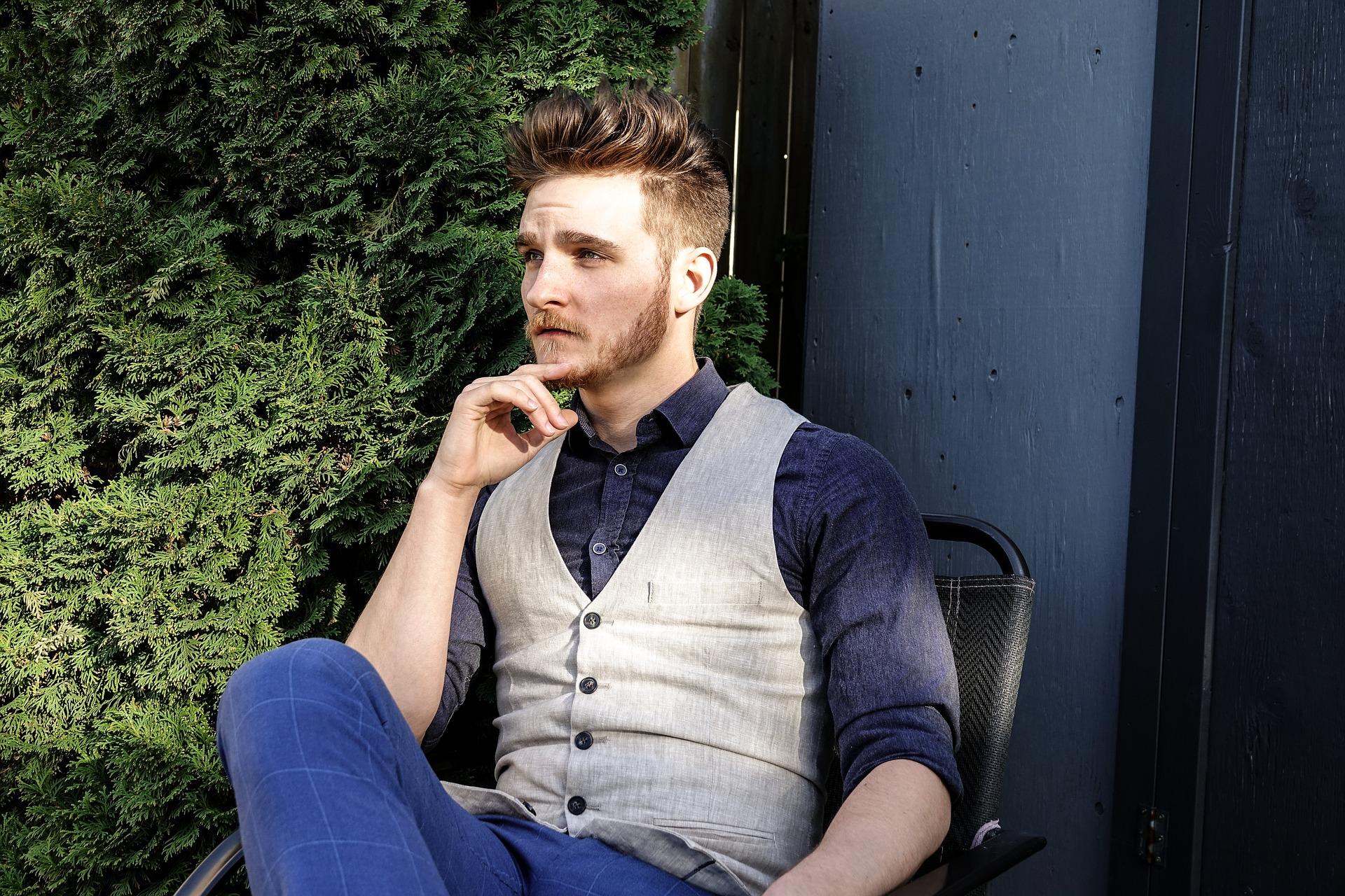 Homme bien habillé assis dehors sur une chaise se touchant la barbe
