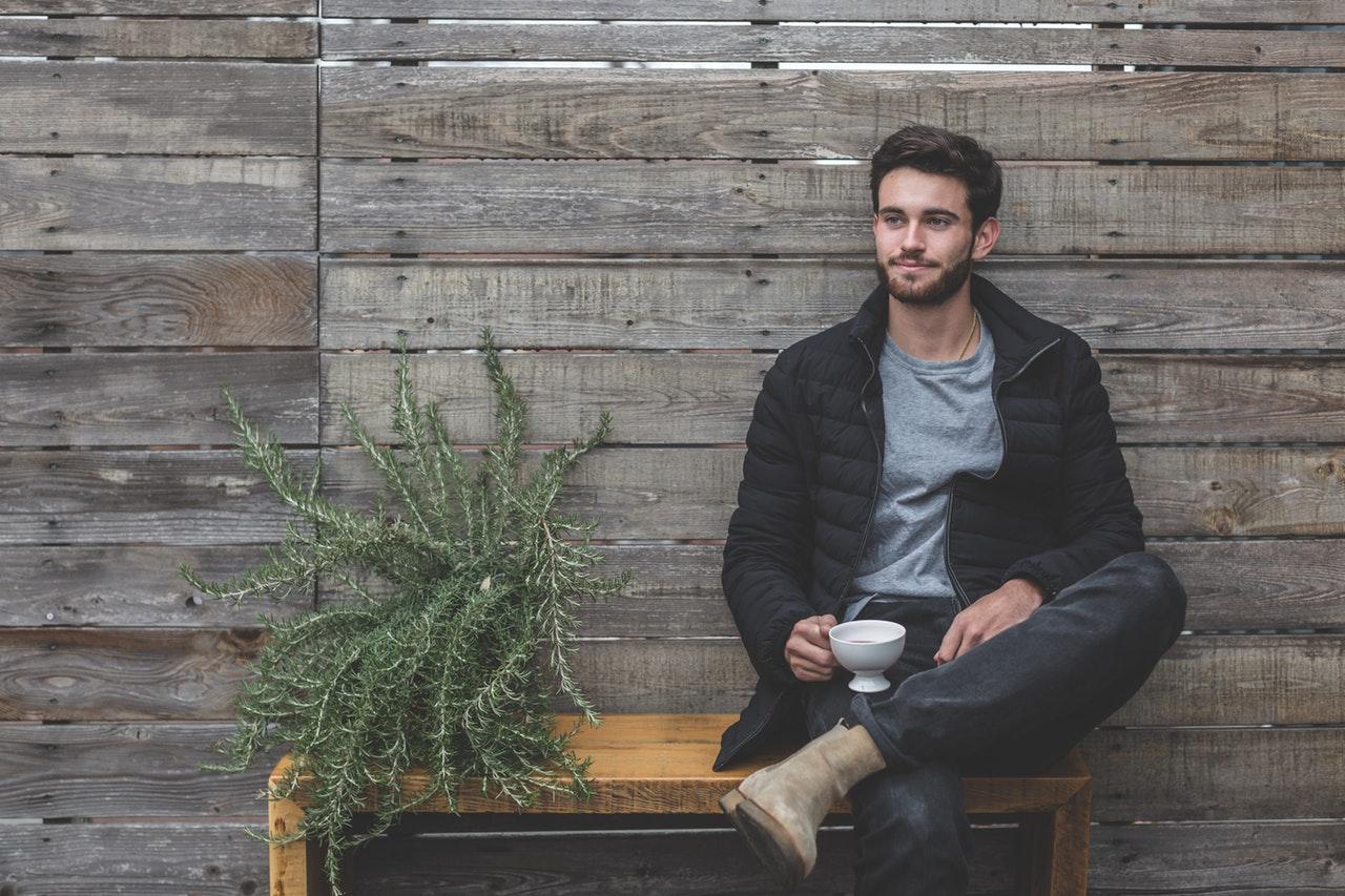 jeune homme assis sur un banc une tasse à la main