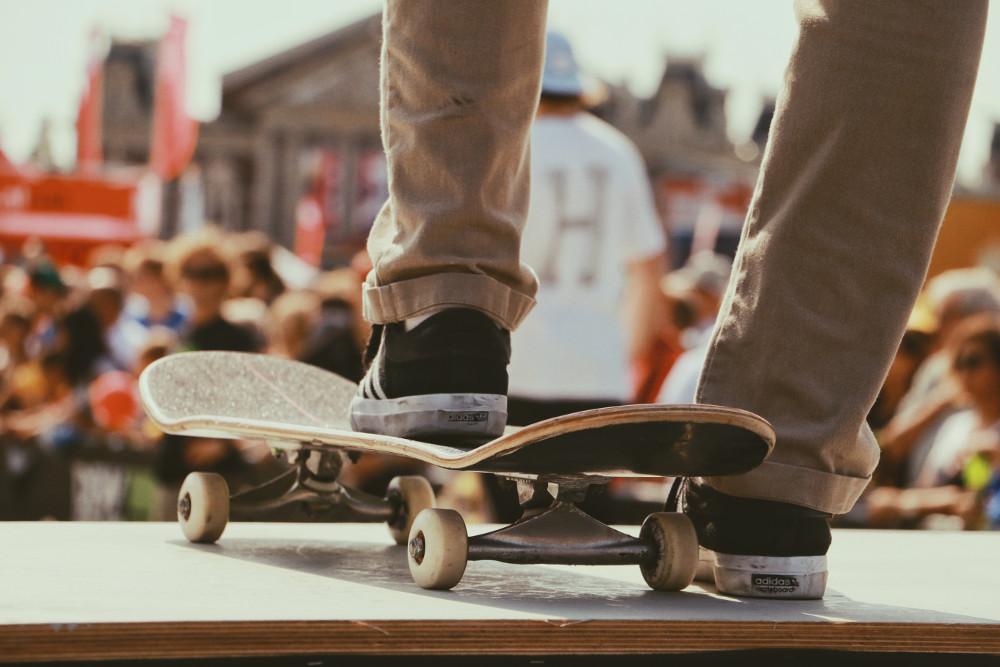 vue sur les pieds d'un homme portant un chino beige et des baskets foncées un pied sur un skate